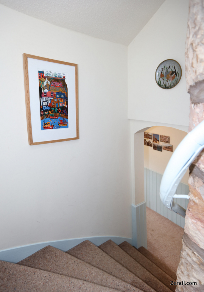 look at the winding staircase within Sandcastle Cottage